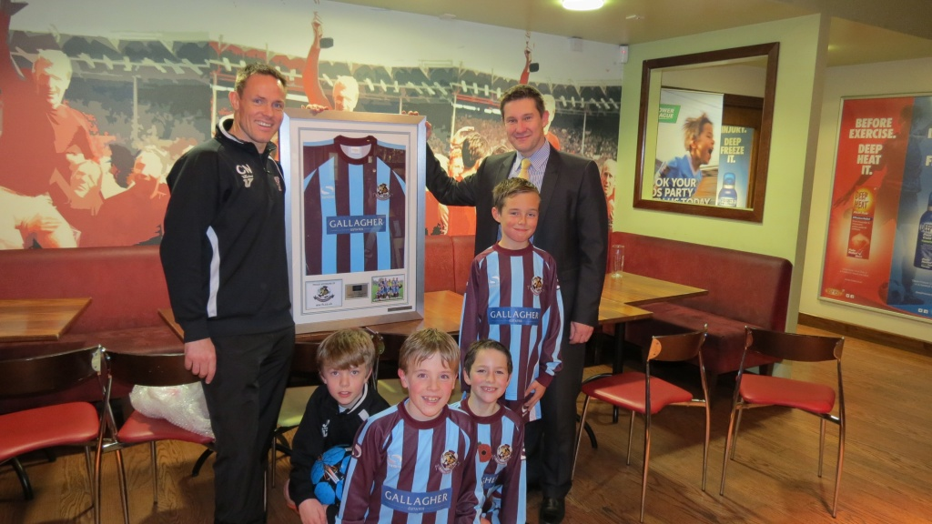 Spencer Claye (Gallagher Estates) receiving a framed shirt from Chris Nicholson (U10 Whirlwinds).